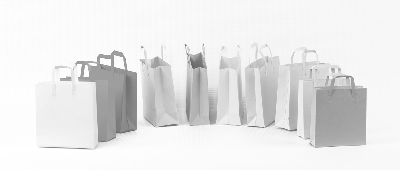 Many bright colored shopping bags standing and layng at random. Isolated image on white background.